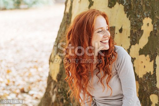 Smiling young woman leaning against the trunk of a tree with peeling bark looking to the side with a beaming smile of pleasure