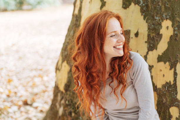 smiling young woman leaning against a tree trunk - woman portrait forest foto e immagini stock