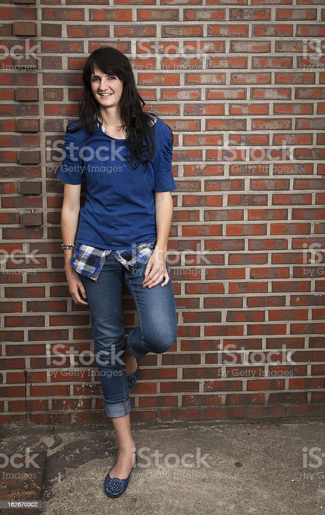 Smiling Young Woman Leaning Against Red Brick Wall stock photo