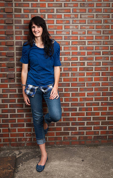 smiling young woman leaning against red brick wall - carolinemaryan stock pictures, royalty-free photos & images