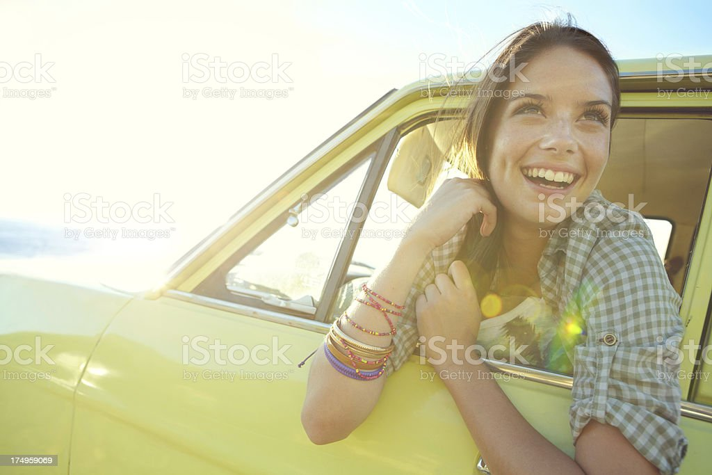 Smiling young woman leaning out of car window royalty-free stock photo