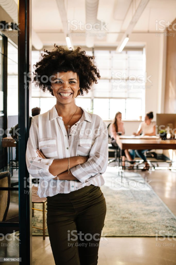Smiling young woman leaning to office doorway stock photo