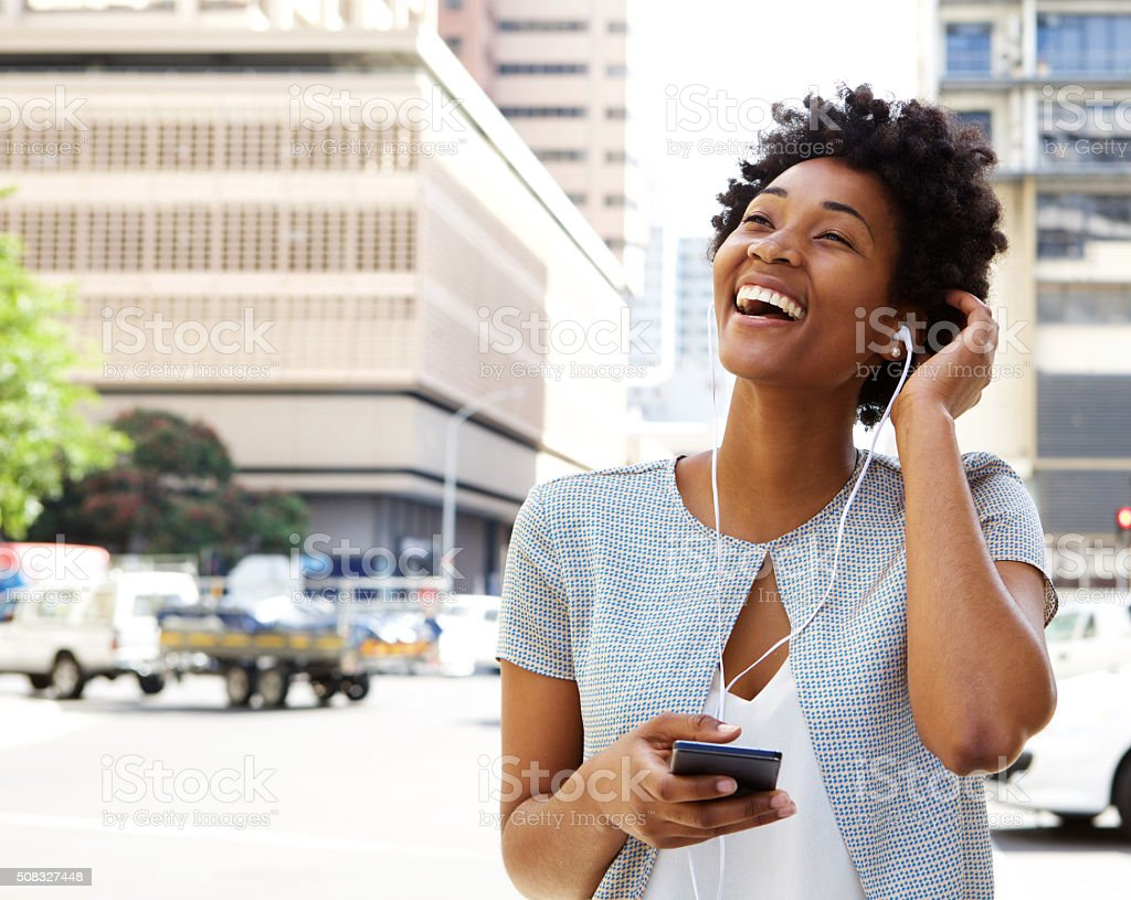 Smiling young woman listening music on headphones stock photo