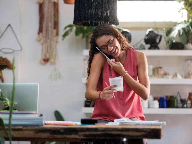 Smiling young woman looking at a receipt paper and talking on the phone stock photo