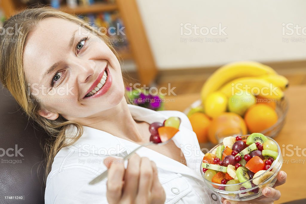 Smiling young woman looking at camera, holding fruit salad, posing royalty-free stock photo