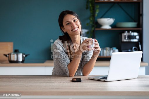 Shot of smiling young woman looking at camera while holding a cup of coffee and working with laptop in the kitchen at home.