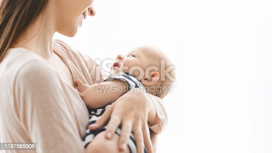 Mother's lullaby concept. Smiling young woman lulling her newborn child in arms, panorama with free space