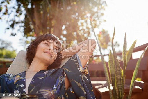 Young woman looking deep in thought and smiling while lying back in a deck chair on her patio on a sunny afternoon