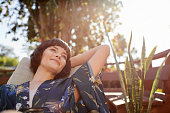 istock Smiling young woman lying back in a patio deck chair 1213507955