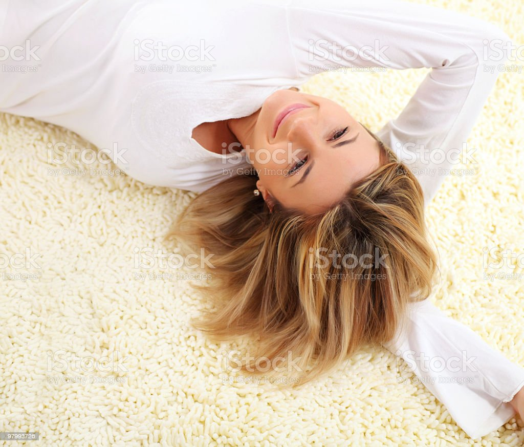 Smiling young woman lying down on carpet. royalty-free stock photo