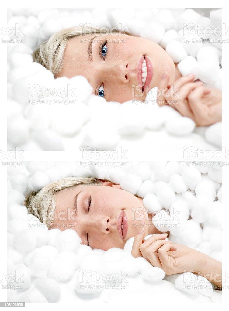 Lächelnde Junge Frau liegen umgeben von Baumwolle Bälle – Foto