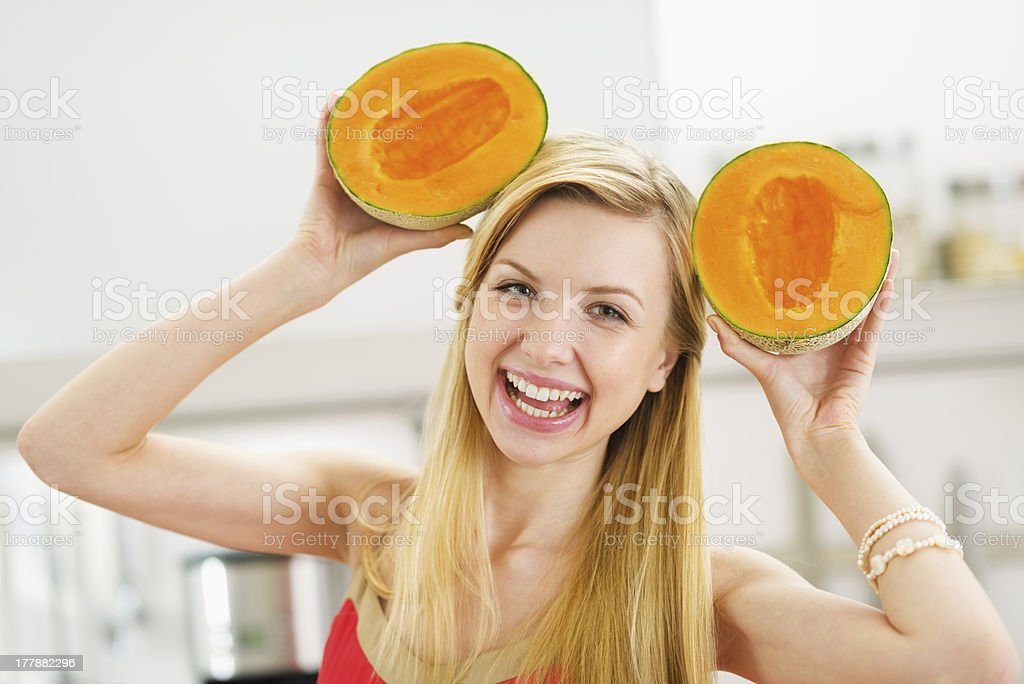 Smiling Young Woman Making Ears With Two Slices Of Melon