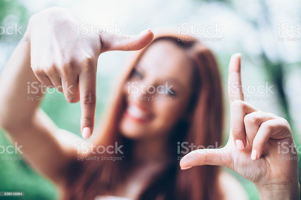 Smiling young woman making frame with hands royalty-free stock photo