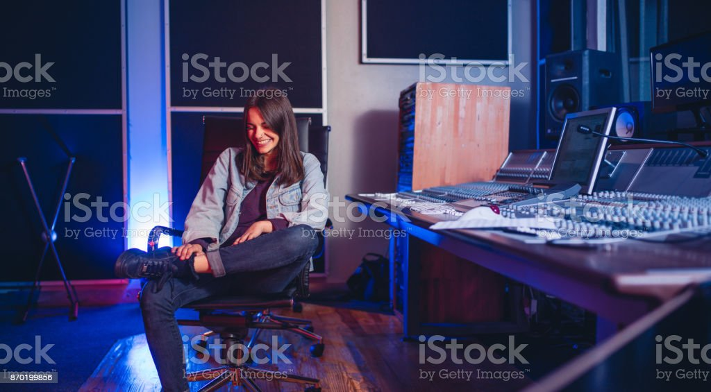 Smiling young woman sitting at music mixing desk. happy female sound...