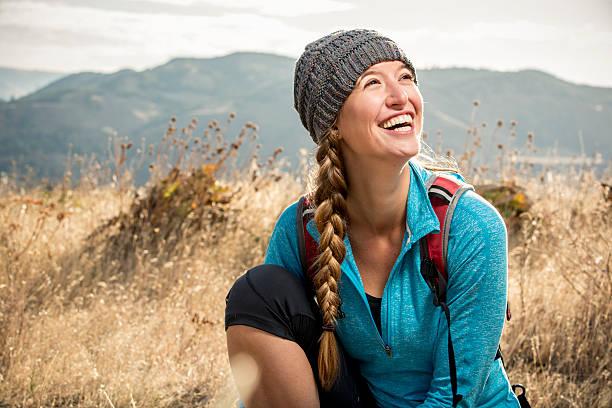 smiling young woman on a hiking trail - vor zöpfe stock-fotos und bilder