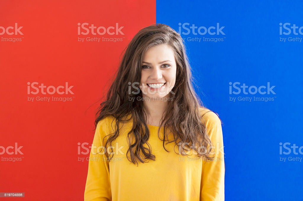 Smiling young woman on blue-red background stock photo