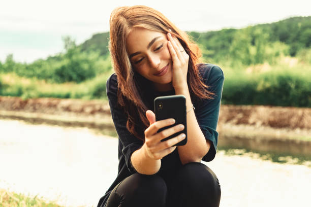 Smiling young woman on video call with Mobile Phone stock photo