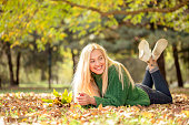 Smiling young woman outdoors in park, falling leaves