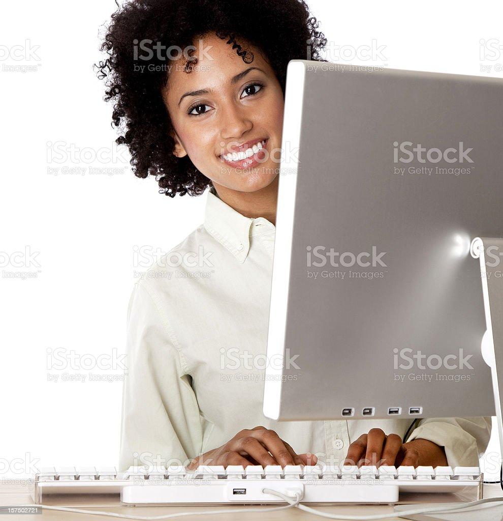 smiling young woman peeking behind computer monitor royalty-free stock photo