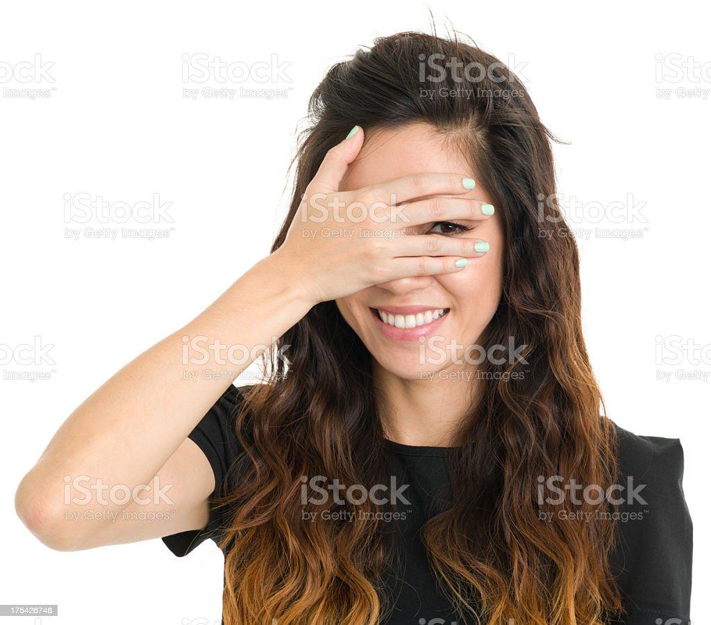 Smiling Young Woman Peeking Through Fingers stock photo