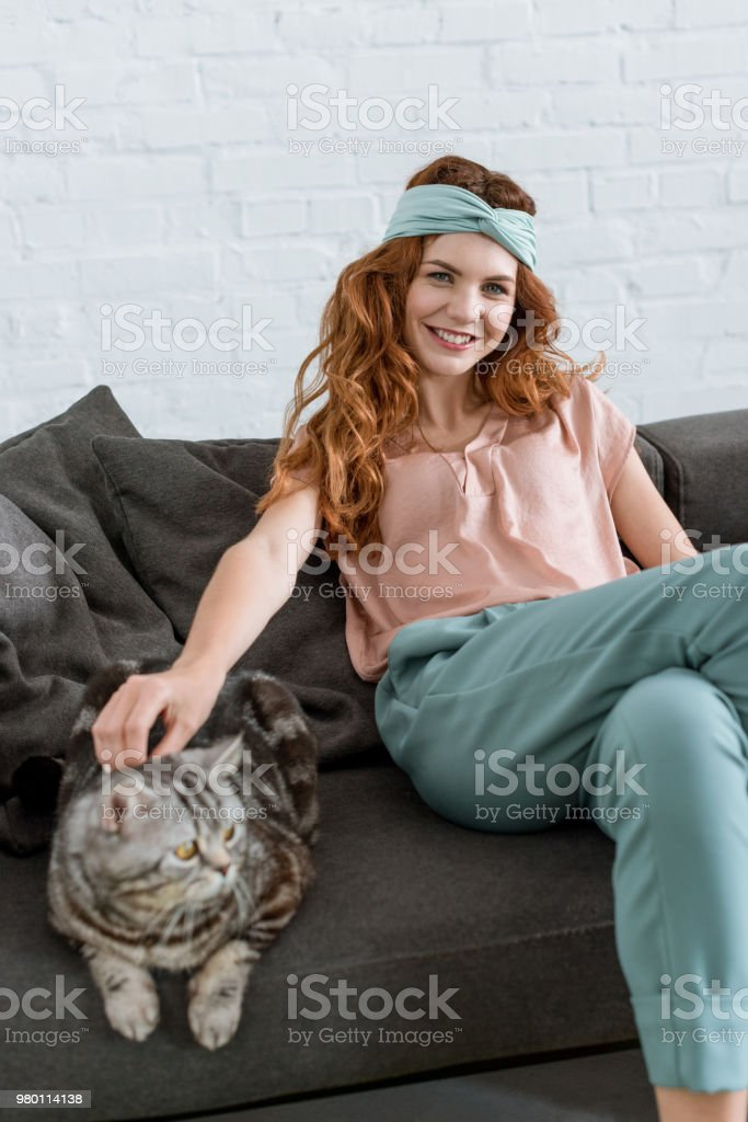 smiling young woman petting tabby cat while sitting on couch at home stock photo