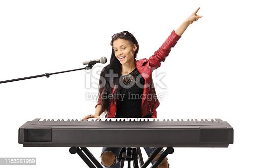Smiling young woman playing a keyboard and singing on a microphone isolated on white background