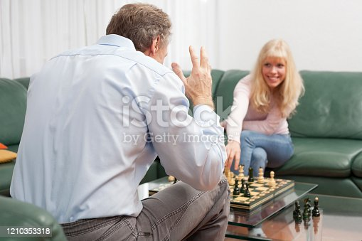 Smiling young woman playing chess with her desperate father - focus on the mature man in the foreground