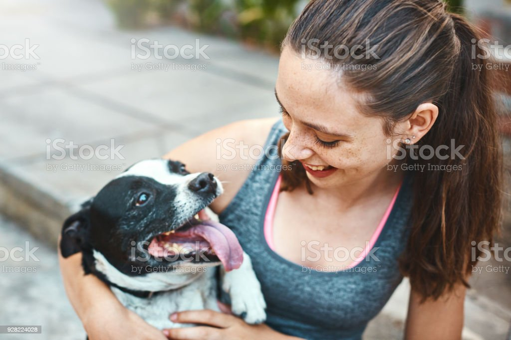 A pretty girl looks down at her pet Staffie as they play together.