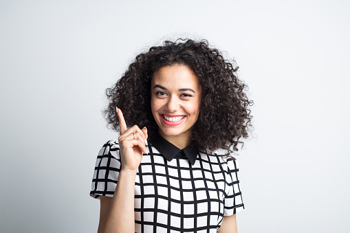 Smiling Young Woman Pointing At Copy Space Stock Photo - Download Image Now