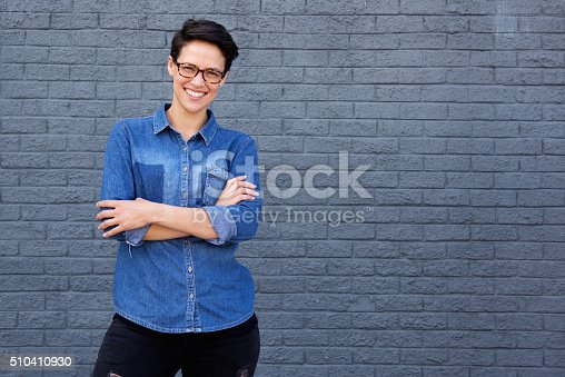 510397772 istock photo Smiling young woman posing with glasses against gray background 510410930