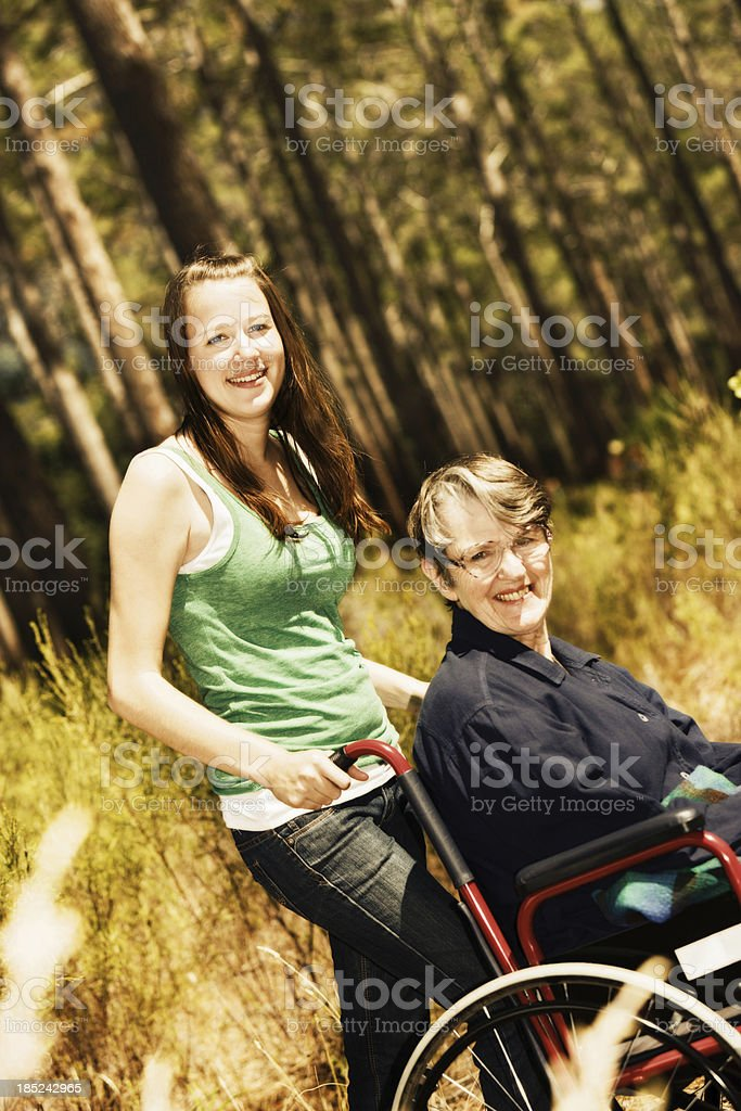 Smiling young woman pushes cheerful grandmother in wheelchair through forest stock photo