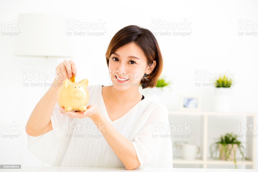 smiling young Woman Putting Coin In Piggy Bank stock photo