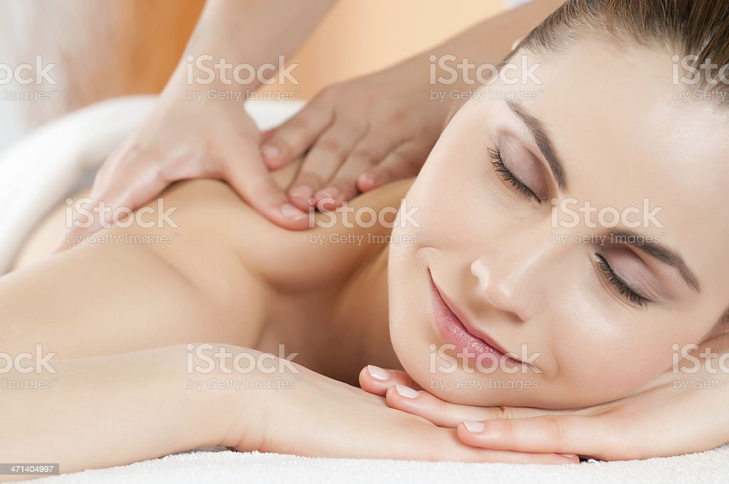 Smiling young woman receiving back massage stock photo