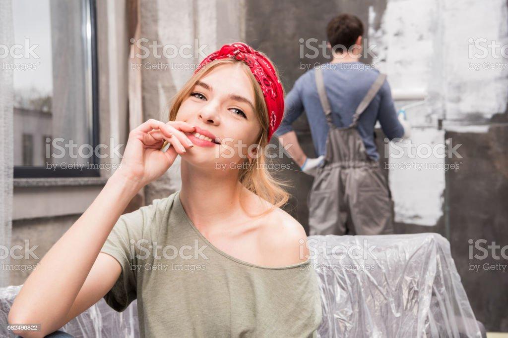 gülümseyen genç kadın kanepe adam boyama duvar, tadilat ev concept süre dinlenme royalty-free stock photo