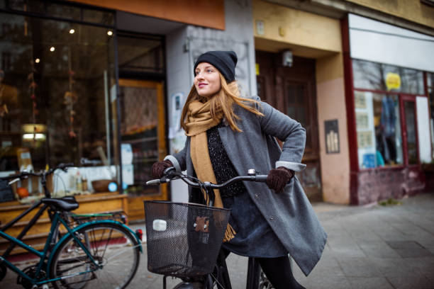 Smiling young woman riding bicycle by building stock photo