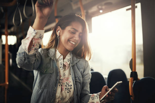 Smiling young woman riding on a bus listening to music stock photo