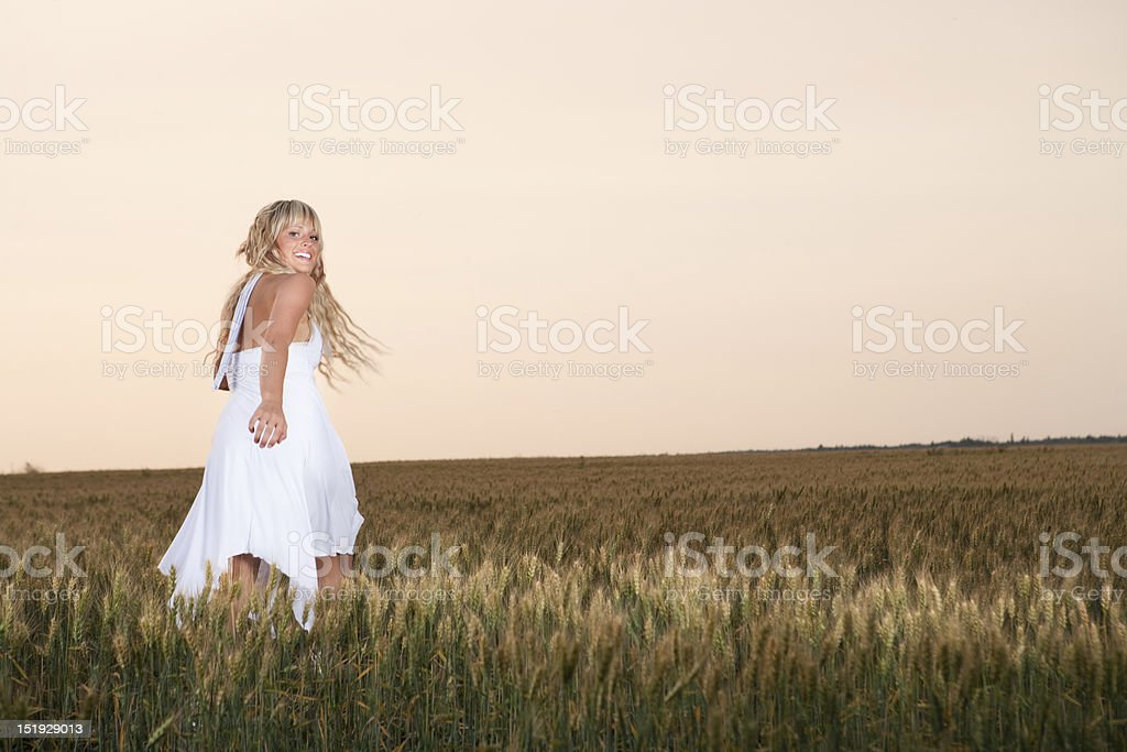 Smiling young woman running in wheat field royalty-free stock photo