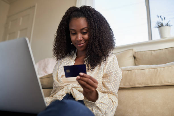 Smiling young woman shopping online shopping from home stock photo