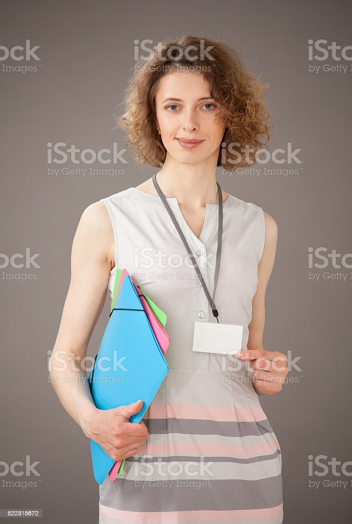 Smiling young woman showing badge stock photo