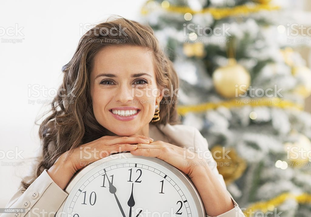 Smiling young woman showing clock in front of christmas tree stock photo