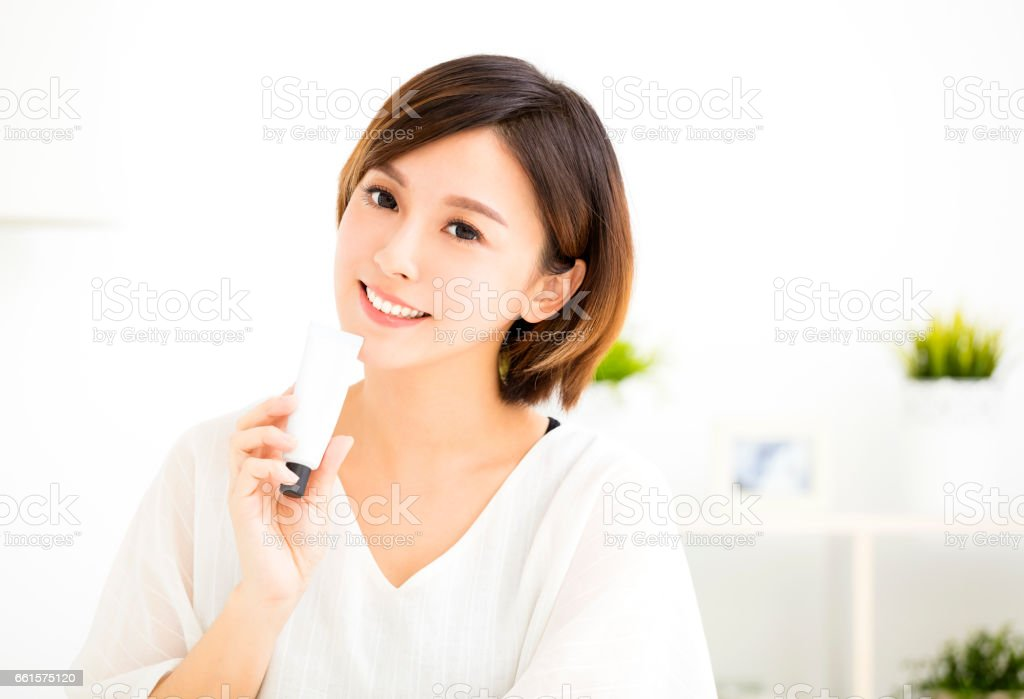 smiling young woman showing skincare products stock photo