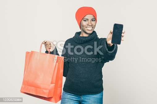1159261513 istock photo Smiling young woman showing smartphone with blank screen 1220520364