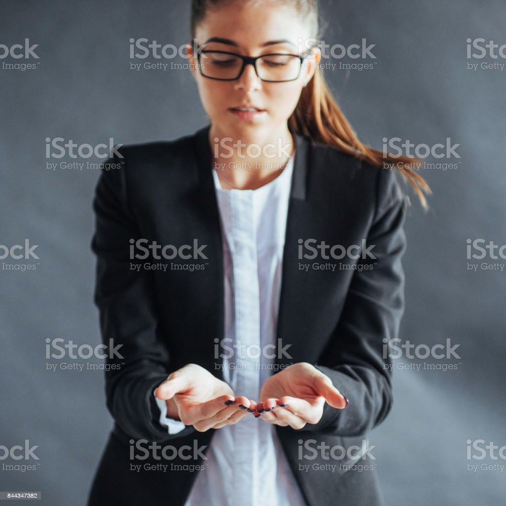 smiling young woman showing something on the palm of both hands open stock photo