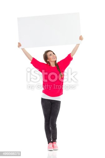 istock Smiling young woman showing white placard 499568075