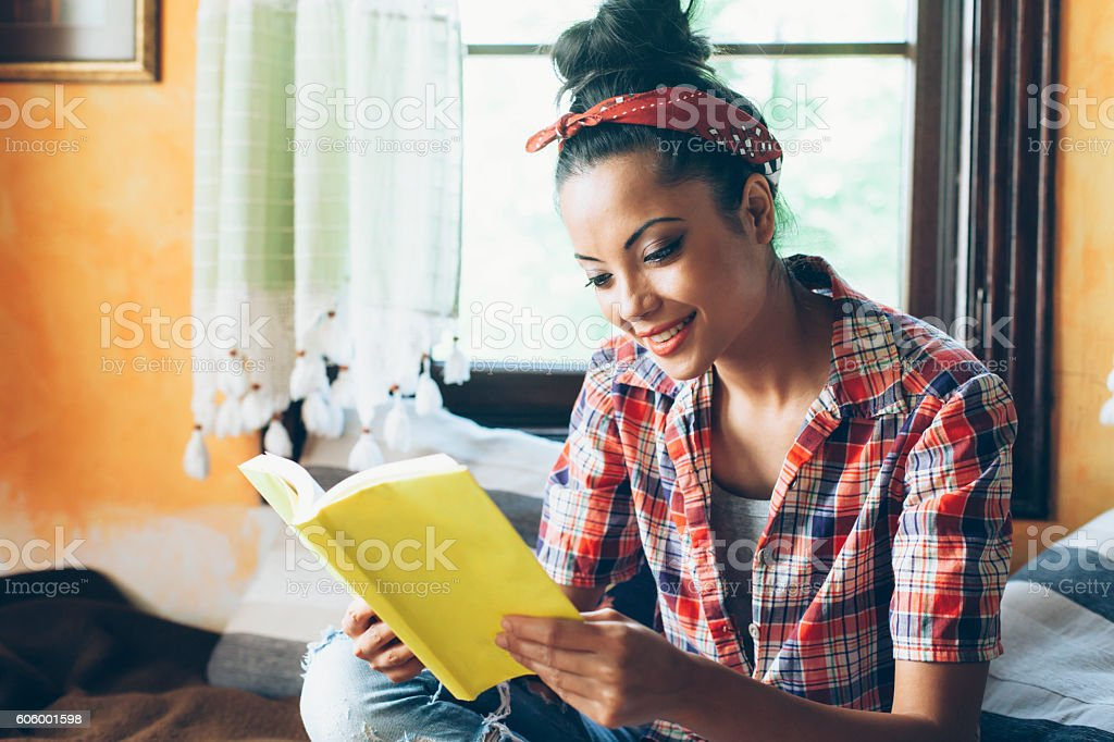 Smiling young woman sitting and reading a book at home stock photo