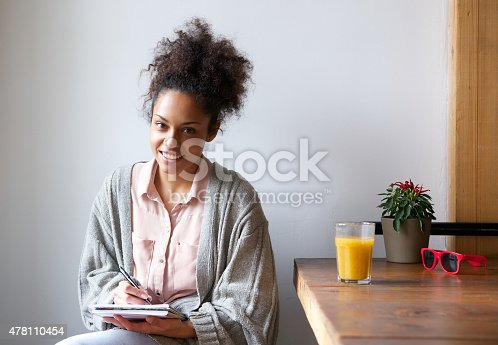 istock Smiling young woman sitting at home writing in note pad 478110454