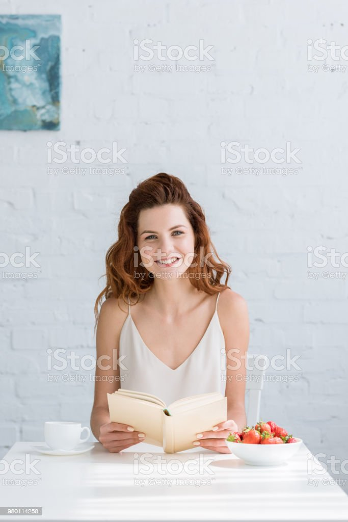 smiling young woman sitting at table with coffee and strawberry and reading book at home stock photo