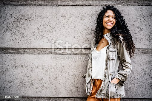 Smiling fashionable woman looking away. Happy female is standing with hands in pockets. She is against gray wall.