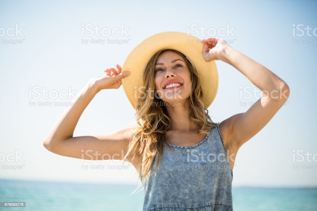 Smiling young woman standing against sky stock photo