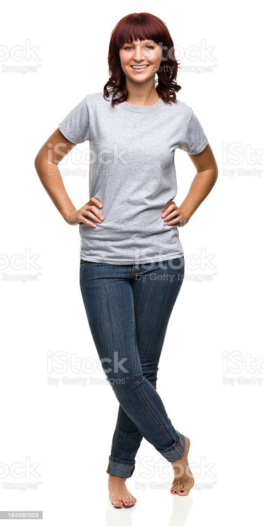 smiling young woman standing with legs crossed stock photo